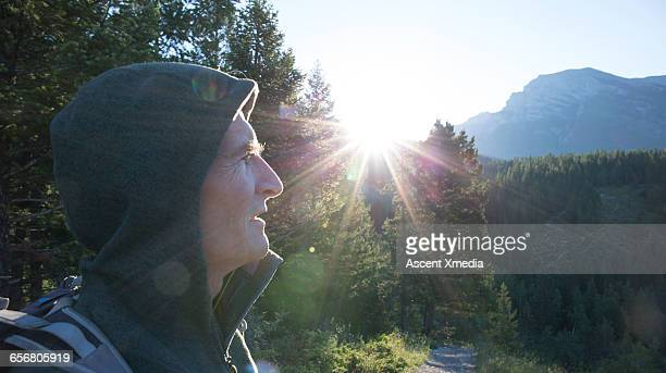 Male hiker looks off to mountains, forest, sunrise