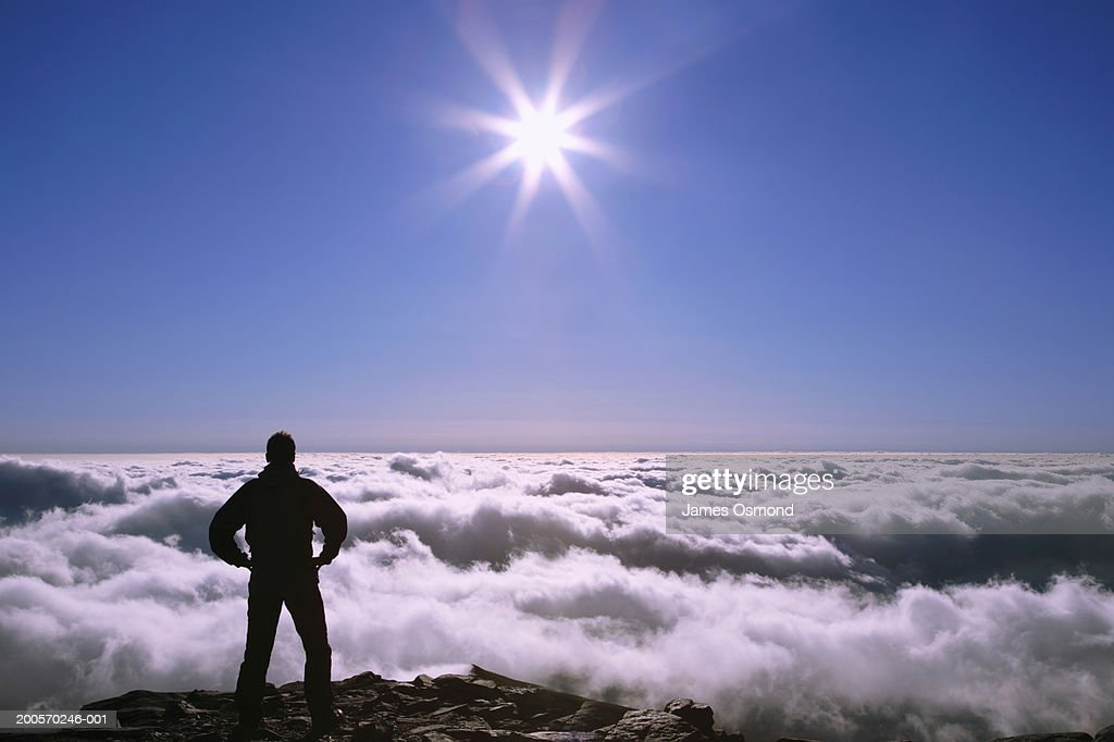 Male hiker on mountain top facing expanse of clouds : Stock Photo