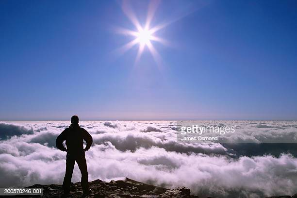 male hiker on mountain top facing expanse of clouds - mount snowdon stock photos and pictures