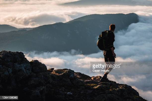 male hiker on summit gazes at mountain rising above clouds, maine - appalachian trail stock pictures, royalty-free photos & images