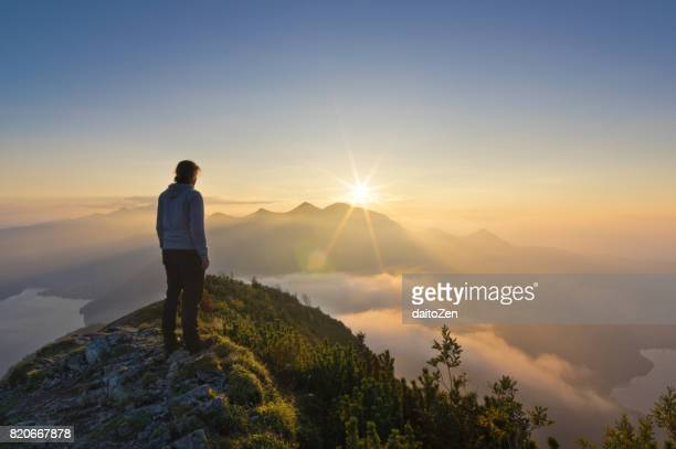 male hiker on summit of jochberg mountain enjoying a splendid sunset, bavaria, germany - mountain peak stock pictures, royalty-free photos & images