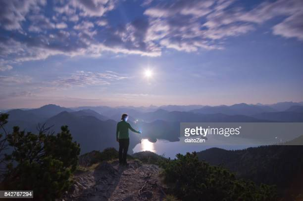 Male hiker on summit of Mt. Herzogstand at night, Lake Walchensee and Bavarian Alps in the background, Upper Bavaria, Germany