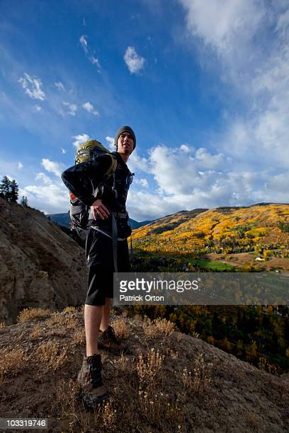 a male hiker overlooks golf course and fall colors in colorado. - avon colorado stock photos and pictures
