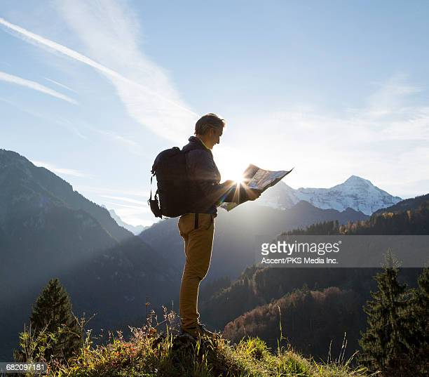 Male hiker pauses on mountain crest, reading map