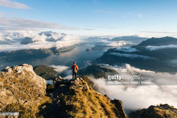 male hiker pauses on ridgecrest above lake, valley - switzerland stock pictures, royalty-free photos & images