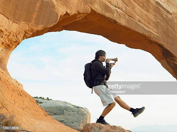 male hiker playing bugle - bugle stock pictures, royalty-free photos & images