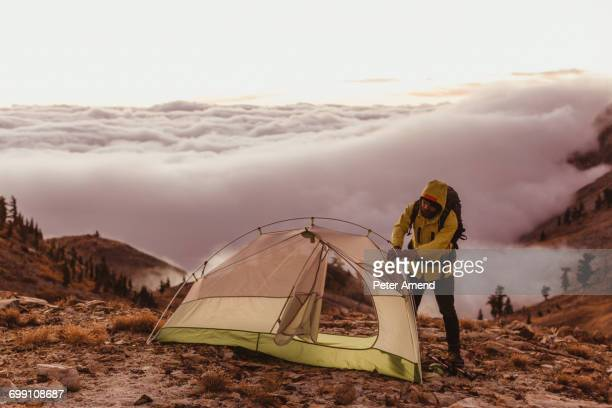 'Male hiker putting up tent above the clouds, Mineral King, Sequoia National Park, California, USA'