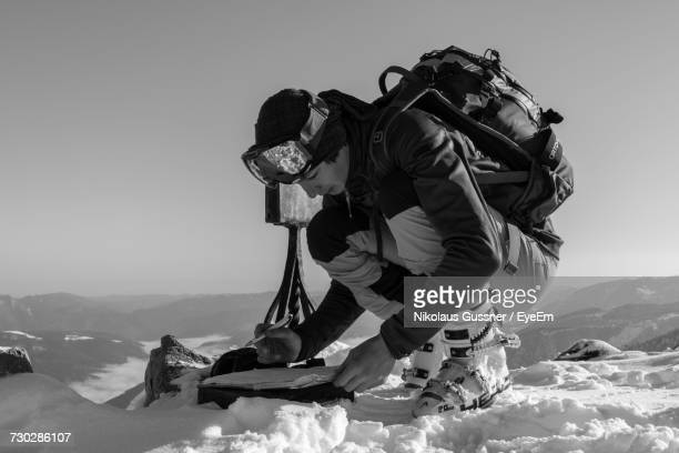 Male Hiker Reading Map At Snow Covered Mountain Against Sky