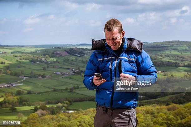 Male hiker reading smartphone texts, Pateley Bridge, Nidderdale, Yorkshire Dales