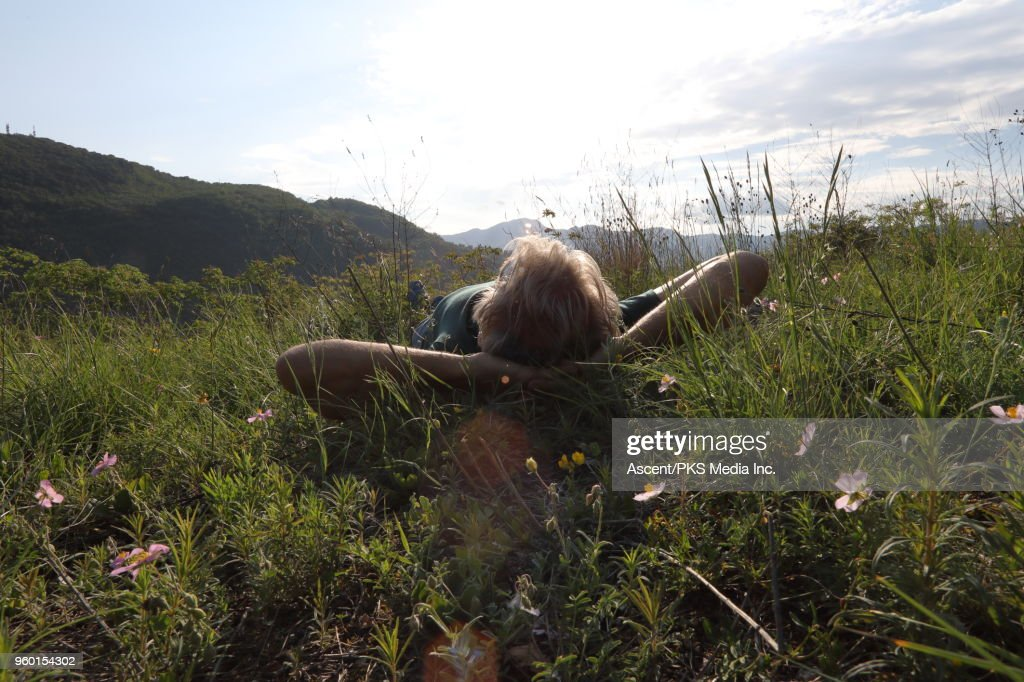 Male hiker relaxes in meadow above distant hills : Stock Photo