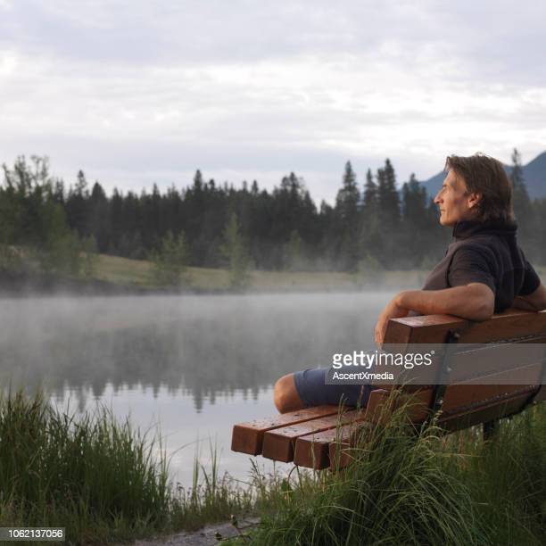 male hiker relaxes on bench at sunrise - sunrise contemplation stock pictures, royalty-free photos & images