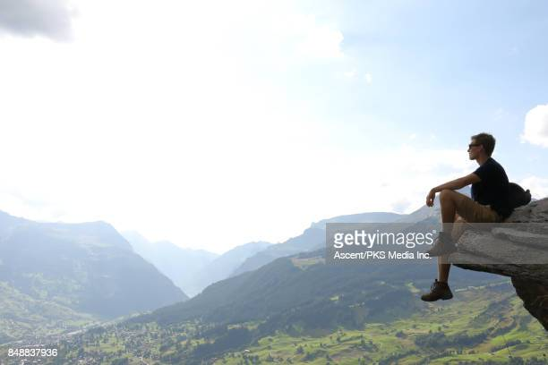 Male hiker relaxes on mountain ledge above valley