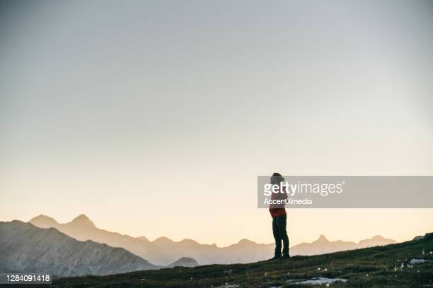 male hiker relaxes on mountain ridge crest - hands in pockets stock pictures, royalty-free photos & images