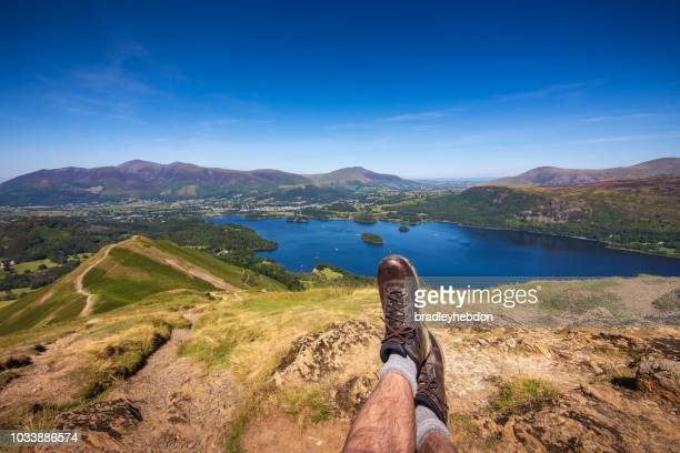 Male hiker resting at summit of Cat Bells looking at Lake Derwentwater and Keswick, England