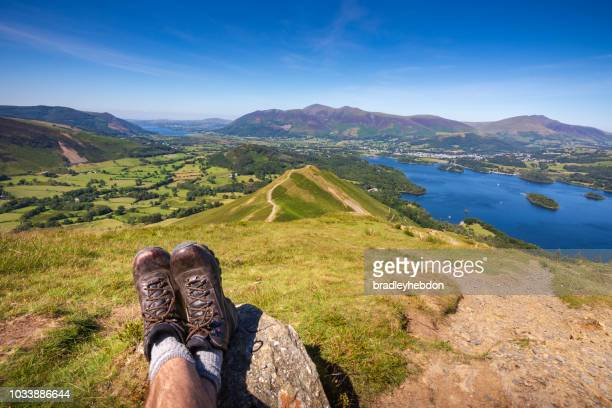 male hiker resting at summit of cat bells looking at lake derwentwater and keswick, england - cumbria stock pictures, royalty-free photos & images
