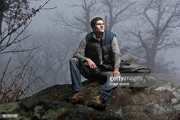 A male hiker sitting on a rock in a misty forest