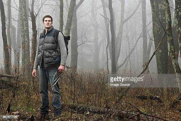 A male hiker standing in a misty forest opening