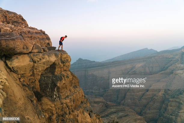 Male hiker standing on edge of cliff above canyon