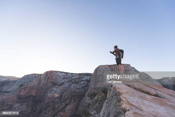 A male hiker stands at the edge of a rock cliff