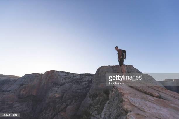 un hombre excursionista se encuentra en el borde de un acantilado de roca - flanco de valle fotografías e imágenes de stock