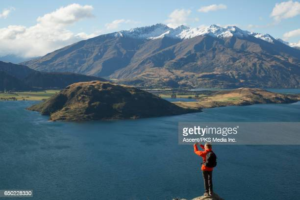 Male hiker stands on mountain ridge, above lake