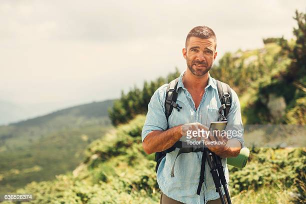 Male hiker texting in the mountain
