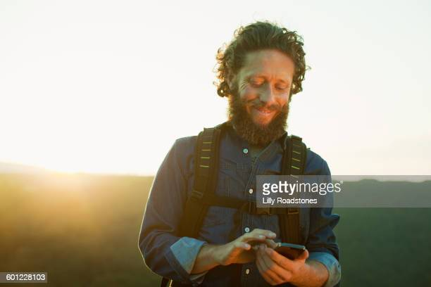 Male hiker texting