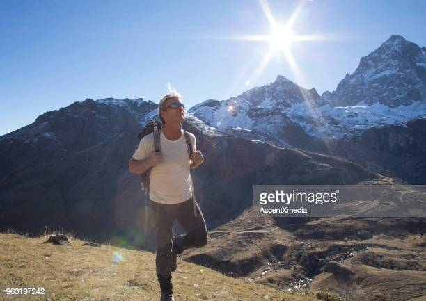 male hiker treks through mountains in sunlight - cuneo stock pictures, royalty-free photos & images