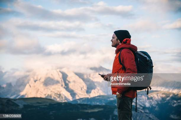 male hiker uses cell phone on mountain ridge crest - red jacket stock pictures, royalty-free photos & images
