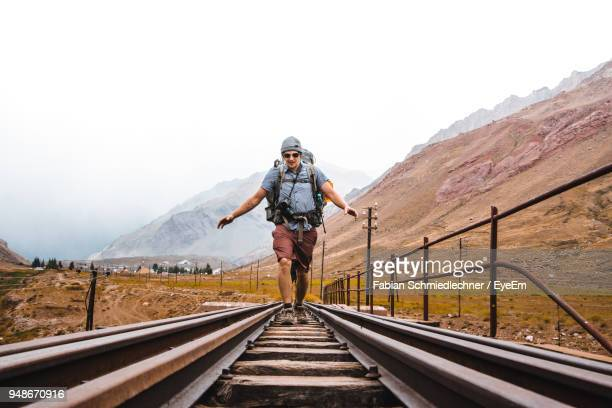 Male Hiker Walking On Railroad Track Against Mountains