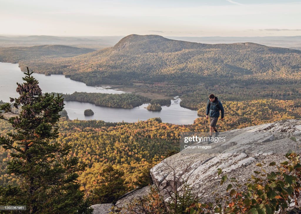 male hiker walks along cliff with view on Appalachian Trail, Maine : Stock Photo