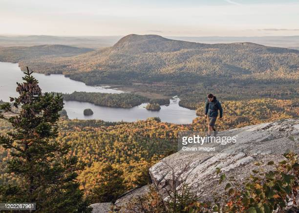 male hiker walks along cliff with view on appalachian trail, maine - appalachian trail stock pictures, royalty-free photos & images