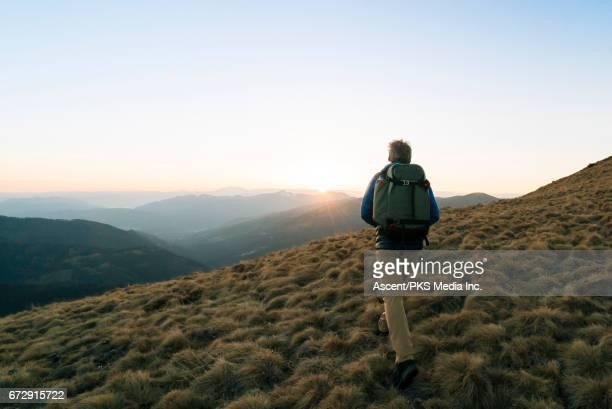 Male hiker walks along mountain summit, sunrise