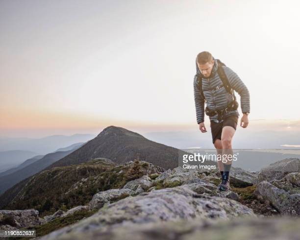 a male hiker walks along the appalachian trail mountaintop in maine - appalachian trail stock pictures, royalty-free photos & images