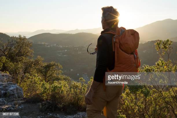 escursionista maschio vaga tra le colline alla luce del sole - tre quarti foto e immagini stock