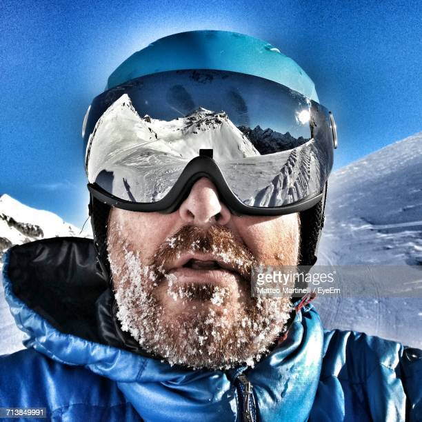 Male Hiker Wearing Ski Goggles With Reflection Of Snowcapped Mountains