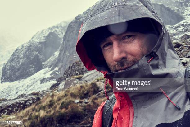 male hiker with hood up in sleeting snow capped mountain landscape, close up portrait, llanberis, gwynedd, wales - weather stock pictures, royalty-free photos & images