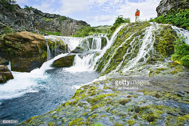 Male hikerhiking alongside waterfall.