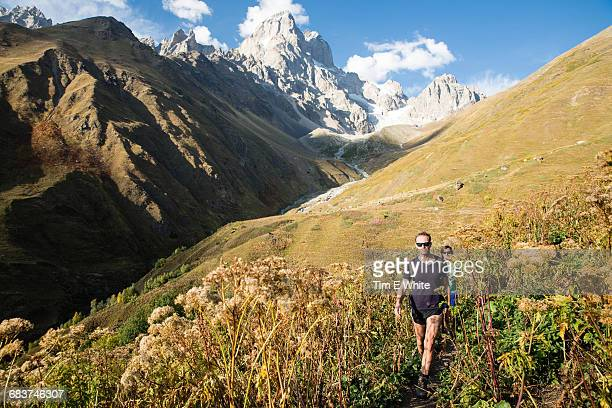 Male hikers hiking in mountain valley landscape, Svaneti, Georgia