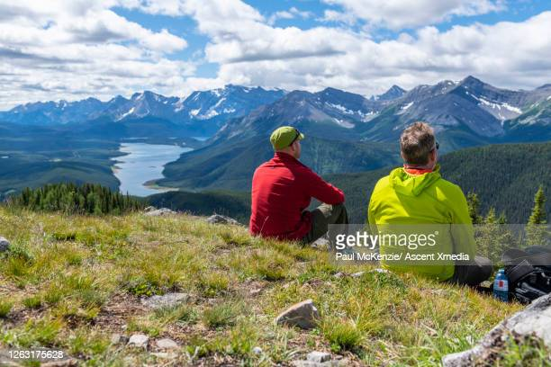 male hikers relax on ridge crest above mountains, valley - kananaskis country stock pictures, royalty-free photos & images