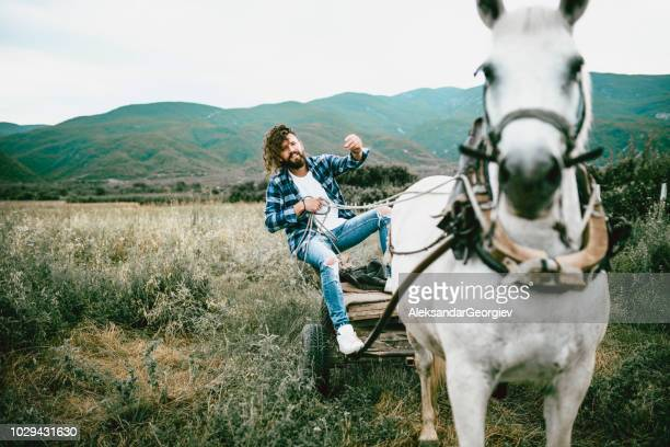male hipster traveling with horse cart through fields - rein stock pictures, royalty-free photos & images