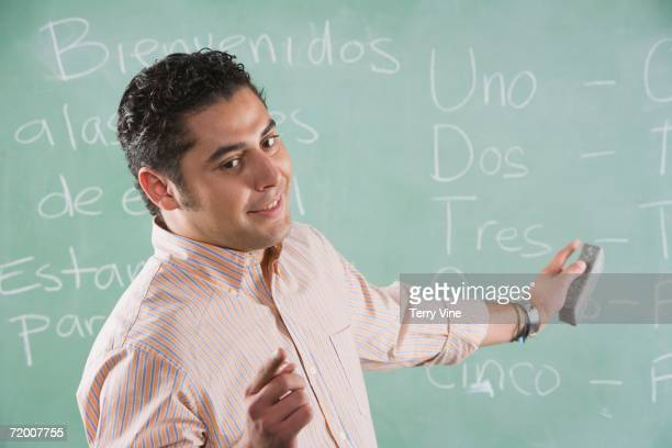 male hispanic teacher at blackboard - spanish culture stock pictures, royalty-free photos & images