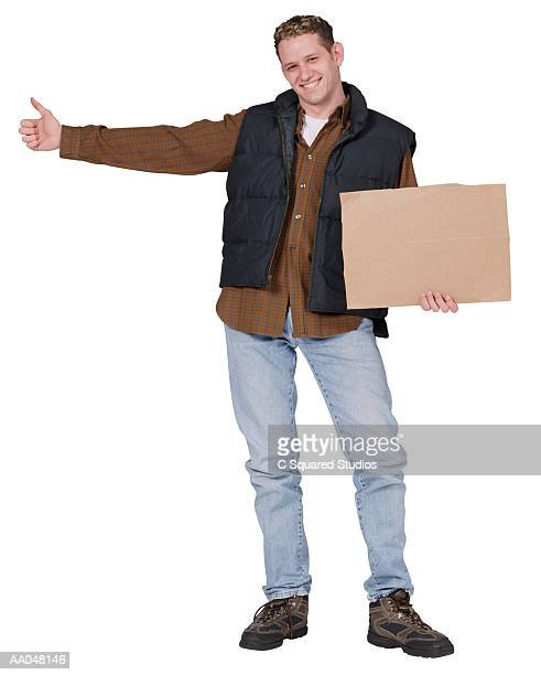 Male hittchhiker pointing finger and holding up blanck sign