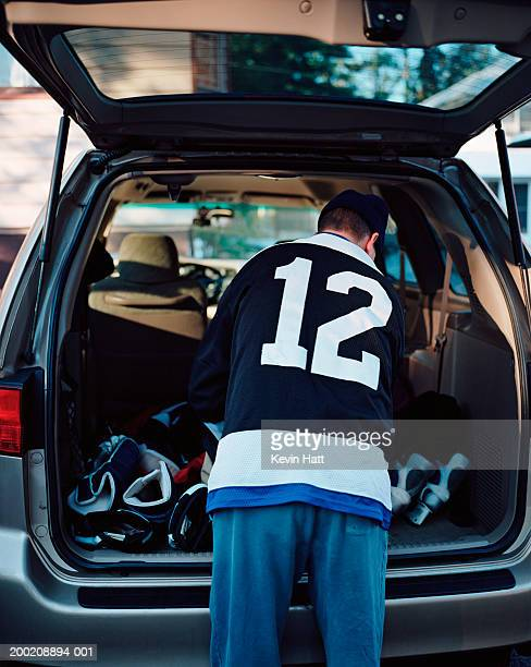 Male hockey player looking in back of vehicle, rear view
