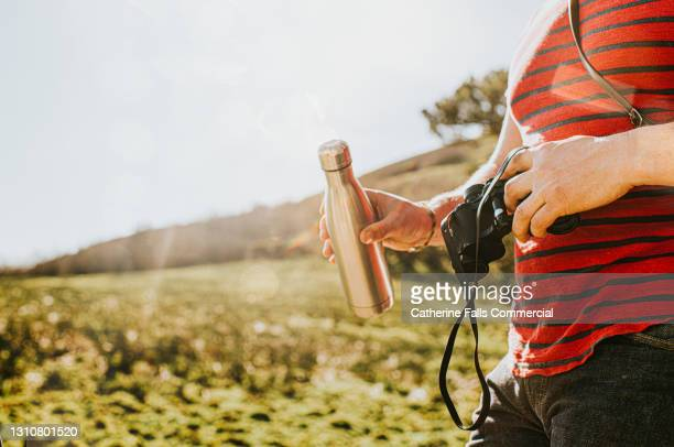 male holding a water-bottle and a pair of binoculars outside - silver shoe stock pictures, royalty-free photos & images