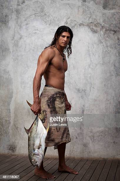 Male holding fish in body wrap on blank wall
