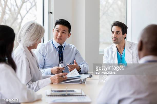 male hospital administrator talks with female doctor - administrator stock pictures, royalty-free photos & images