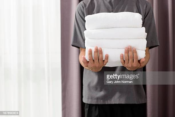 male housekeeper in hotel holding towels - タオル ストックフォトと画像