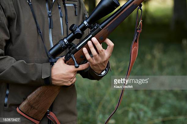 male hunter loading his rifle - rifle stock pictures, royalty-free photos & images