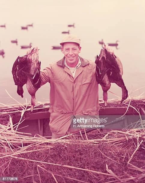 male hunter proudly holding up four dead ducks. (photo by h. armstrong roberts/retrofile/getty images) - 20th century stock pictures, royalty-free photos & images